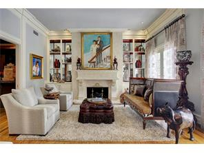 The formal living room is accented by the cast stone fireplace and a wall of French Doors that open to the pool and grounds in back