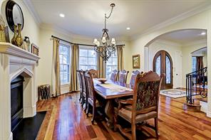 FORMAL DINING ROOM with three large windows overlooking the front yard, a gas-log fireplace with cast stone mantel, and a lovely traditional chandelier.  This room will accommodate dining tables of various sizes and shapes.