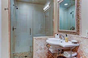The PRIVATE ATTACHED BATH to BEDROOM 5 on the first floor has a large shower with frameless glass enclosure, pedestal sink with towel storage, tumbled marble wainscot and built-in mirror with mosaic tile frame.  Beautiful !