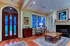 The ENTRY with beveled glass door and transom opens to the formal living room which further opens to the study via 2 divided light French doors.  There is a dual sided fireplace between the study and the living room.  The dining room is out of view.