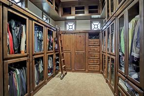 A view of the master closet on the opposite side. The rolling library ladder ensures maximum space efficiency so that the high ceiling storage is not wasted. Built-in shoe racks and organizers make getting ready a breeze.