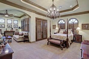 The second master bedroom on the second floor has its own balcony and spacious sitting area. Lovely wood plantation shutters line the windows for privacy and the tray ceiling showcases the dramatic crystal chandelier.