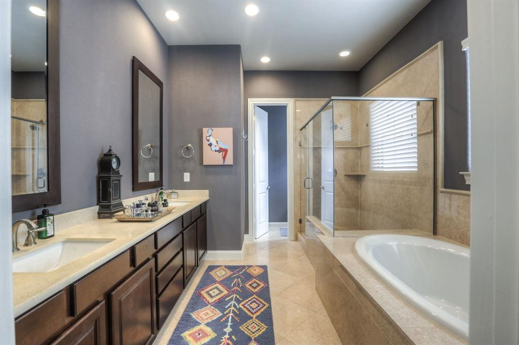 Master bath with dual vanities, separate tub and shower and natural stone tile floor.