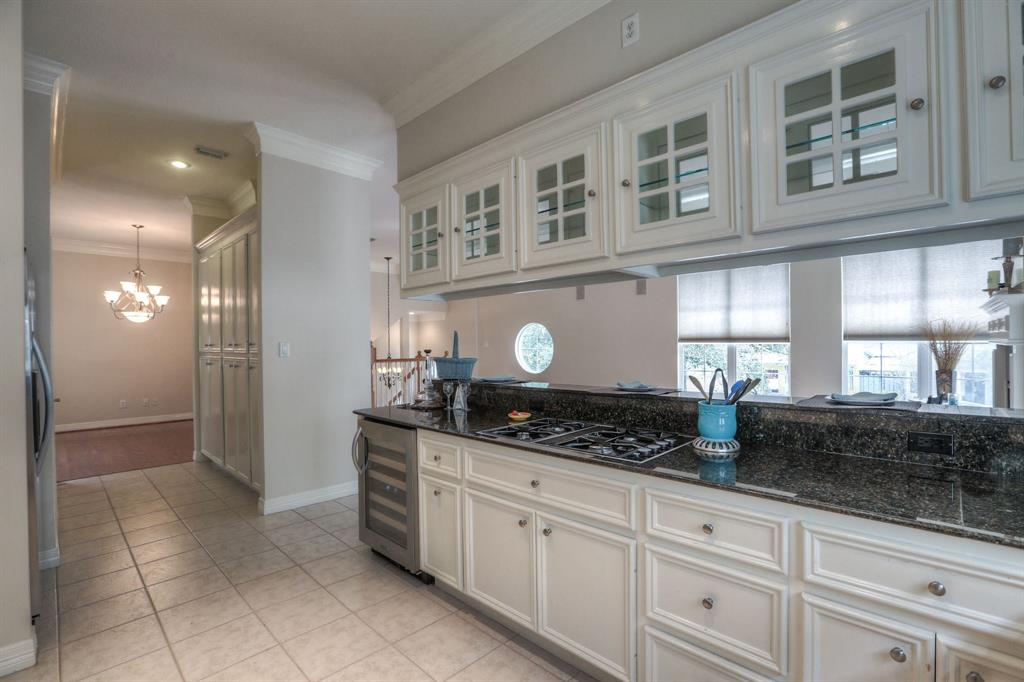 The kitchen also includes gas powered cooktop, a wine fridge, and a large pantry space.