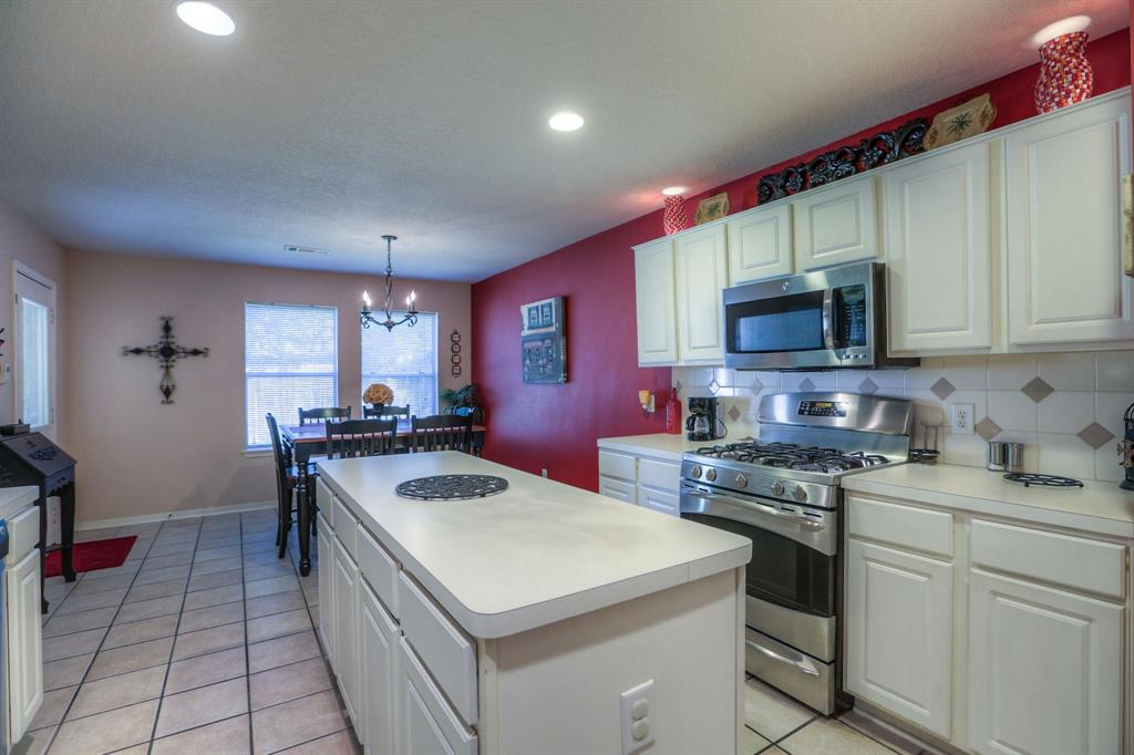 The kitchen also includes a large pantry, tile floors, and stainless steel appliances.
