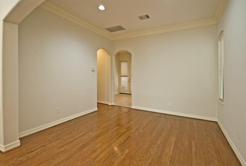 Dining space is open to the living room and features wood floors and crown molding.
