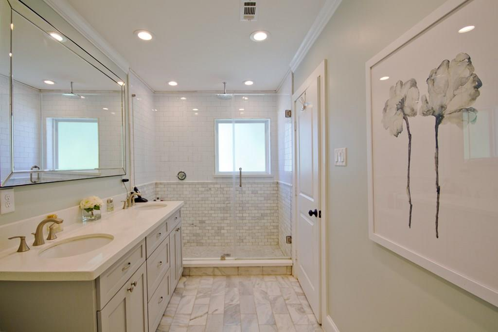 The ensuite master bathroom features a walk-in rain head shower, double sinks, quartz countertops, and marble tiling on the floors and shower surround. The walk-in master closet connects to the bathro