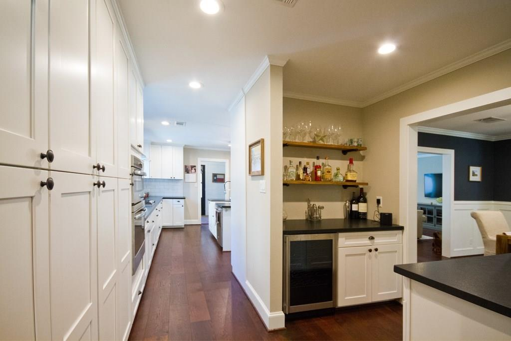 The butler's pantry that connects the kitchen and dining room features a built in dry bar complete with wine fridge.