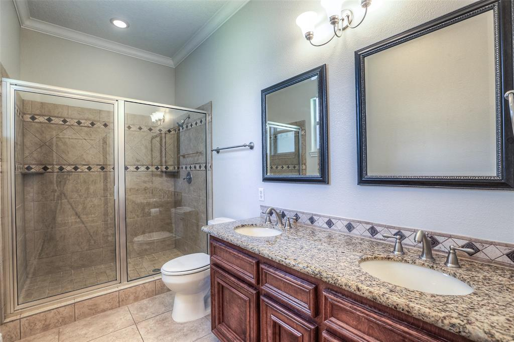 Hall bathroom with dual vanities and large shower.