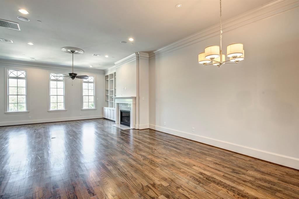 Light and bright view of the spacious open concept dining and living rooms with hardwood floors, crown molding and high ceilings with built in surround sound speakers.
