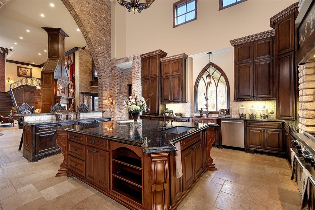 Other architectural details that spice up the epicurean experience include a pitched beamed ceiling, white stone surround and vent around the five-burner gas stove, tiered granite breakfast bar that seats four, and built-in china cabinet.