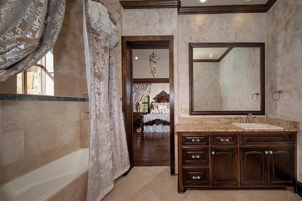 The bath is appointed with granite vanity, tile flooring, custom hues on walls, and a glass enclosed bathtub and shower.