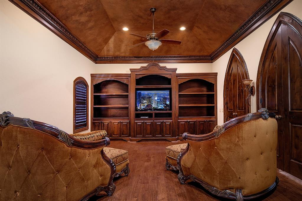 The recreational rooms are accessed through pointed archways and wood doors off the upstairs gallery walkway. The game room features a tray ceiling painted in wood hues to match its hardwood floor. A massive built-in with space for a large screen monitor is flanked by open and covered storage space that anchor the room at one end. An arched window with functional custom wood plantation shutters controls the natural light allowed into this area.