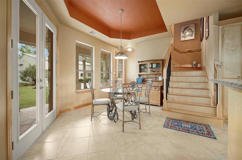 Enjoy breakfast, snack, or any meal in the casual eating area alongside large windows that bring the outside in.More wonderful builder details of tray ceiling, wrought iron spindles, tasteful wood balusters, and wood stair steps leading to half story where spacious game room is located.