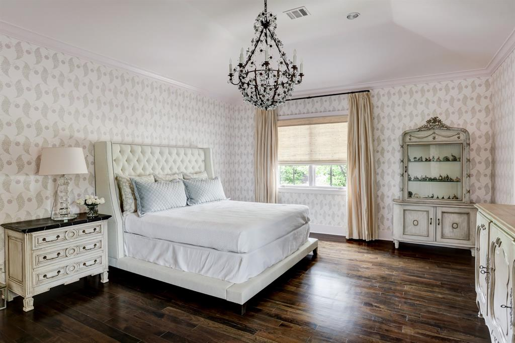 The primary bedroom has high ceilings, hardwood flooring, his and her baths, northern light and a views to the side walled garden.