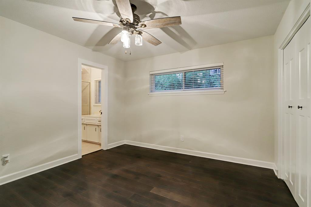 This secondary suite features two large closets, a ceiling fan, treetop views and a private bathroom.