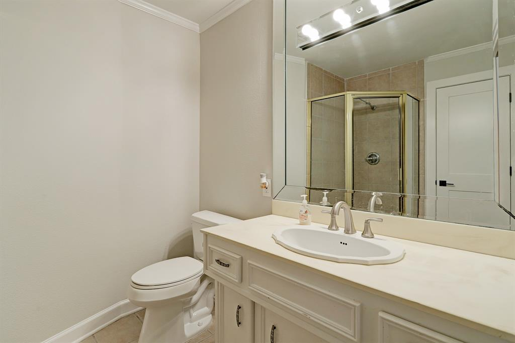 This full bathroom — accessible from both the hall and a secondary bedroom suite — boasts a corner shower stall and fantastic vanity lighting.