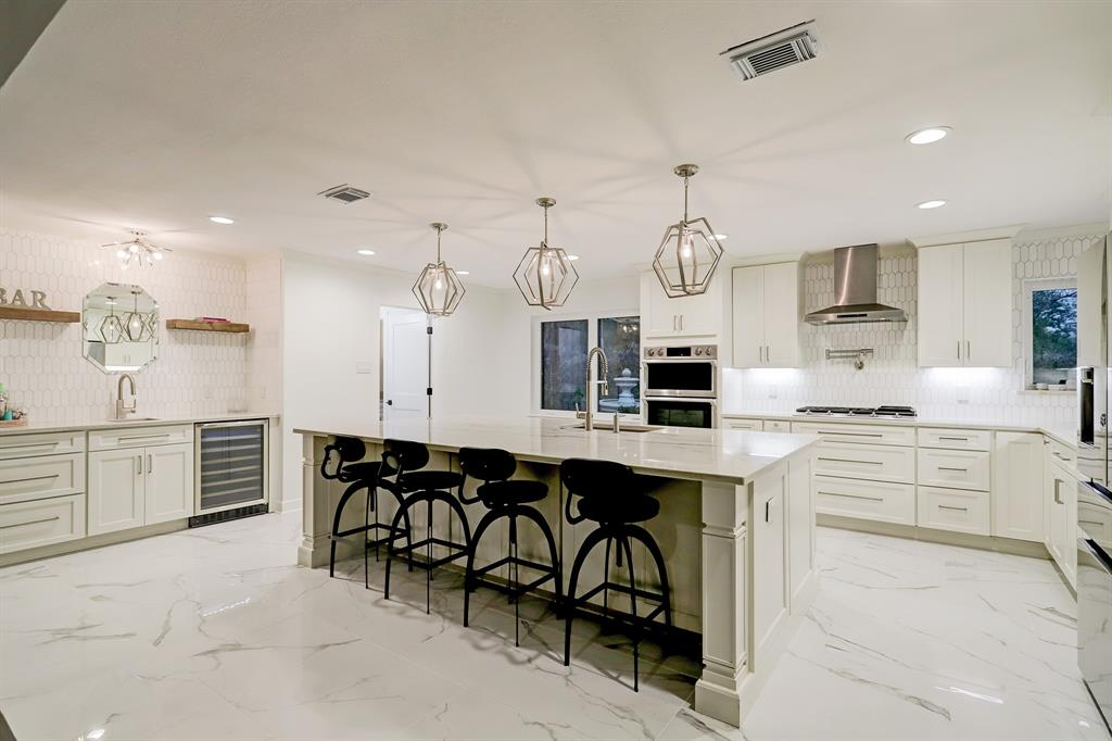 This expansive open kitchen dazzles with gleaming stone floors and counters, custom cabinetry and gorgeous designer lighting.