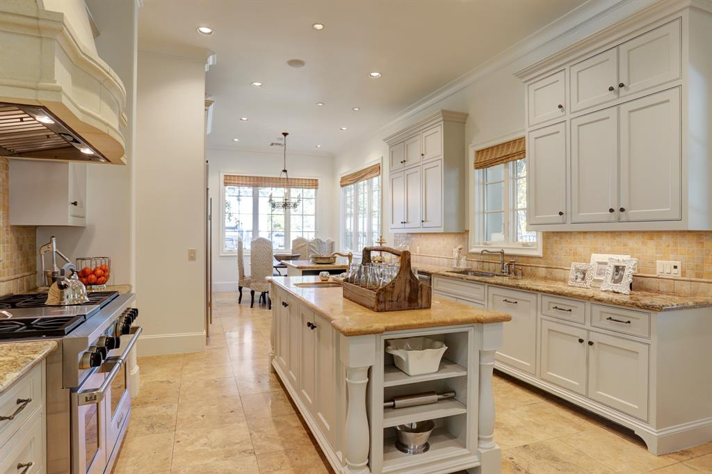 Another view of the KITCHEN - a gourmet cooks delight ! Lots of stained wood cabinets for storage, granite countertops and top of the line appliances. The granite topped center island features a utility sink with decorative fixtures.