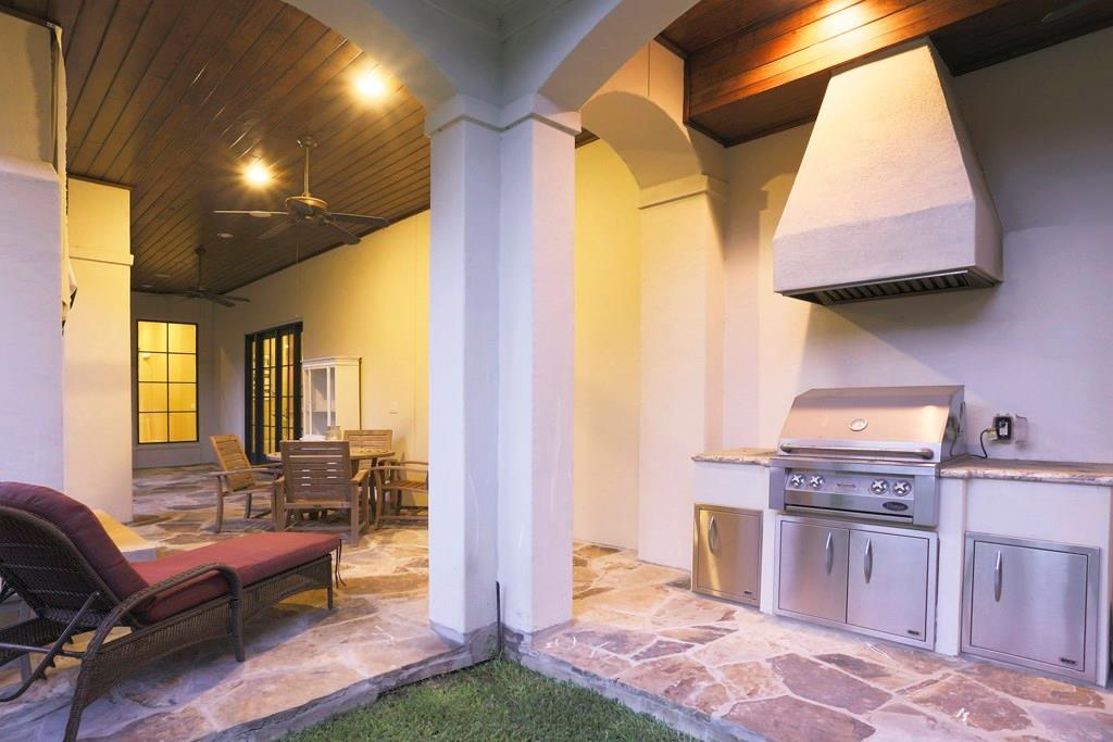 The OUTDOOR KITCHEN is just beyond the outdoor living area and includes the same slate flooring and wood planked ceiling.  Noteworthy is the built in stainless gas range with  cabinet doors below, granite counter top and handsome stone vent hood.