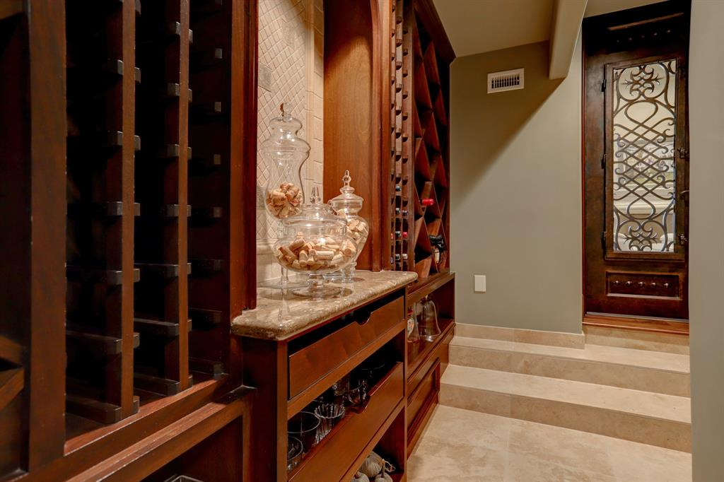 Another view of the WINE ROOM - this one showing the notable wood/glass/wrought iron detailed doorway and steps downward to the spacious area which is surrounded by built-in cabinets/drawers/bottle storage.