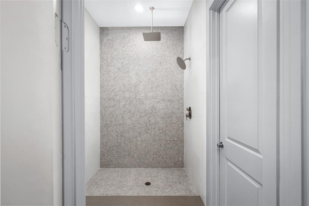 Double rain shower heads and water closet with access to both sinks on the other side of each door.  Awaiting installation of glass shower doors.