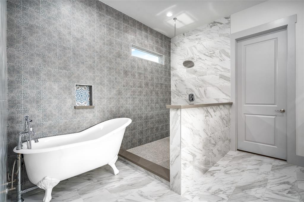 Artfully designed tile inlay features a floral pattern in blue- the perfect accent color for the monochromatic color scheme.  Awaiting installation of shower glass above pony wall.
