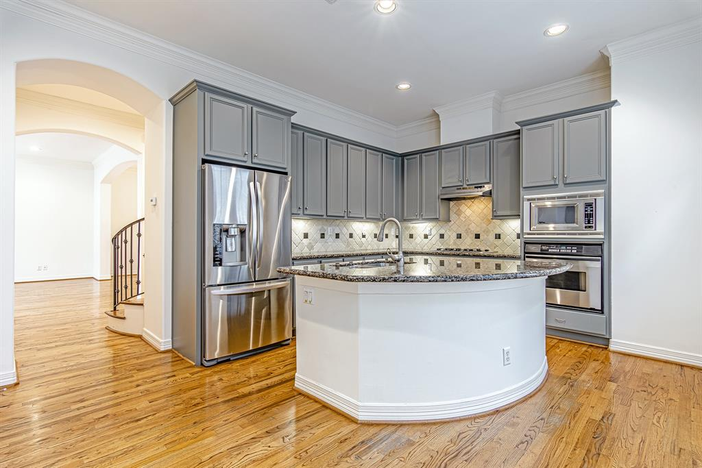 This is the kitchen with island and breakfast bar. Beautiful SS appliances and hardwood floors aith custom colored cabinets.