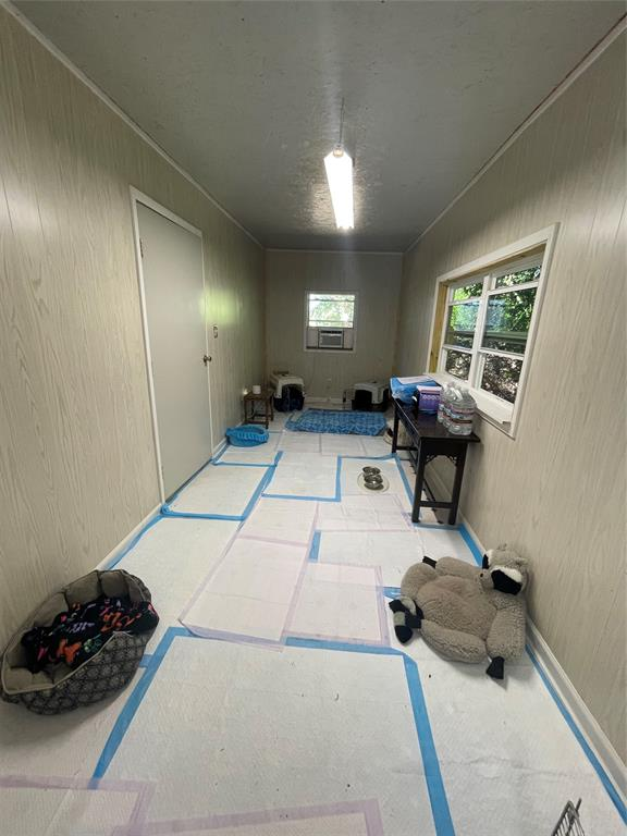 This room is attached to the carport.  Currently used as a doggie house.  Completely with a/c, new tile flooring (floor currently covered) and finished out and painted