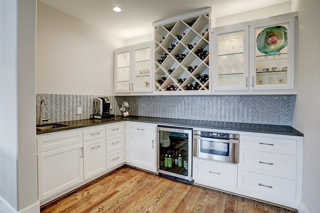 Bar in gameroom with wine fridge and storage, microwave, bar sink, and glass cabinets.