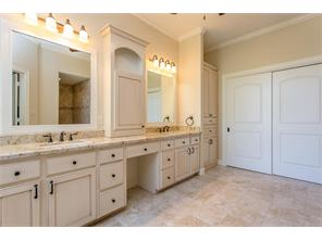 When you enter the Master Bath this is what you see. Note the Faux Painted Site Built Cabinetry, Double Sinks,  Granite Surfaces, Tile Flooring. In the mirror you can see a reflection of the Walk in Shower. The Double Doors lead into the Closet.
