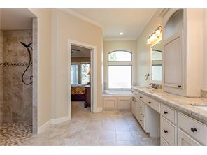 From the Master Closet you can see the soaking tub and the tiled walk in shower with seat.