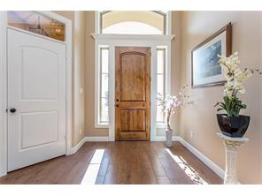 The entryway with Sidelights, a Transom Window and Crown Molding above the Solid Wood Entry Door. Notice the Transom Window above the Door to the Mudroom & Garage.