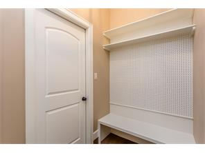 The Mud Room has a Bench to sit and change your shoes and a PegBoard so you can arrange your hooks for jackets, umbrella, etc. Through the Door is the Garage.