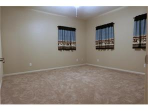 "The first of two bedrooms upstairs.  Lots of windows with 2"" faux blinds, plush carpet and huge walk-in closet"