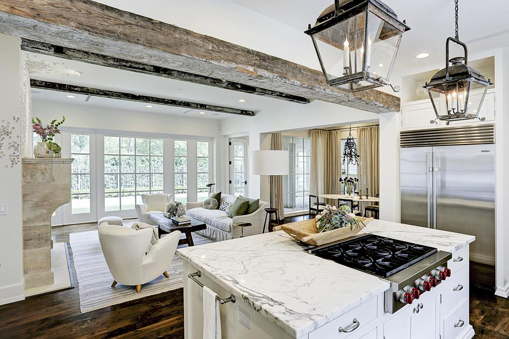 Elegant white kitchen by M Naeve in a French inspired home with rustic beams, antique reclaimed doors, and walnut floors