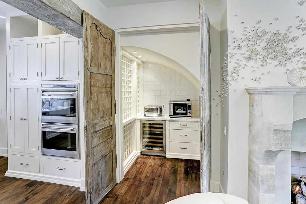 Kitchen pantry with antique rustic door in elegant white kitchen by M Naeve