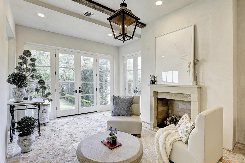 A stunning white enclosed loggia in a Houston home by M Naeve with lantern and reclaimed Chicago brick floor