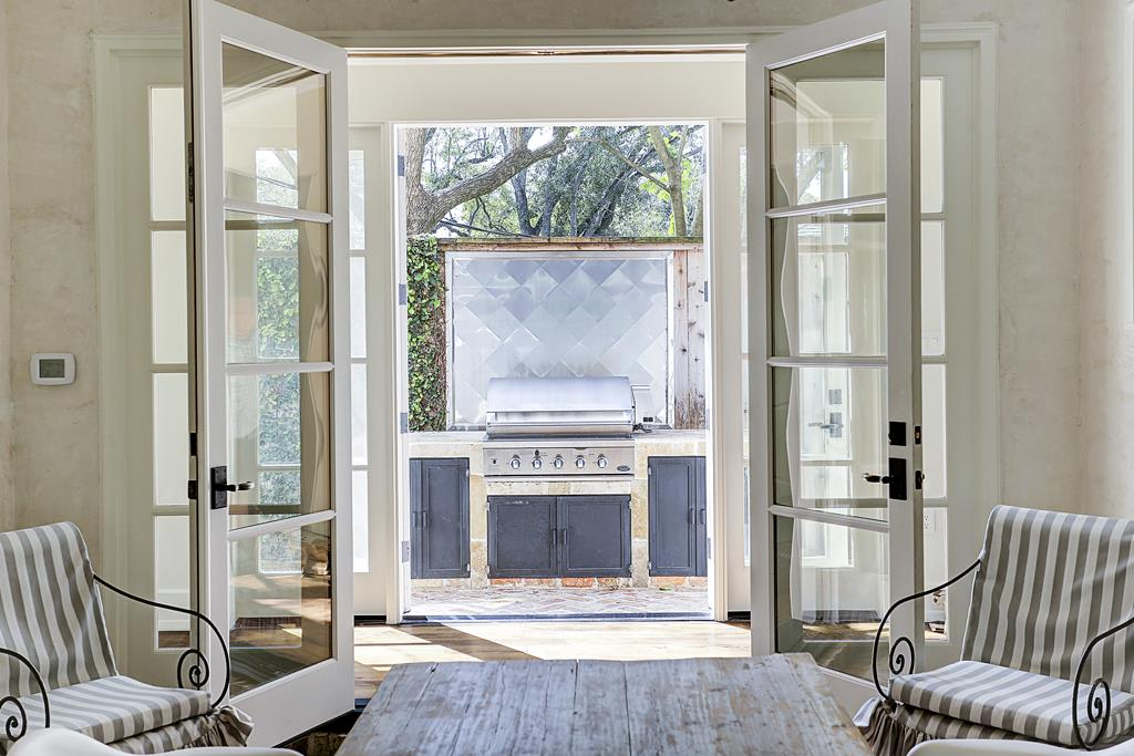 French doors to grill patio area near enclosed loggia in elegant Houston home by M Naeve