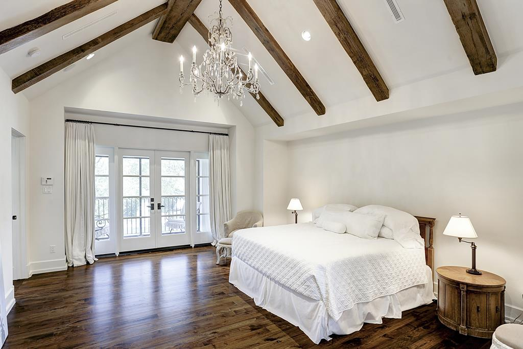 Walnut floors and beams in white bedroom with French doors in elegant Houston home with French inspired interiors by M Naeve