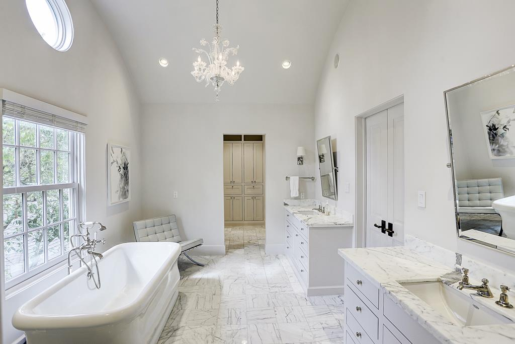 Gorgeous and luxurious white bathroom with high ceiling in elegant French inspired Houston home with interiors by M Naeve