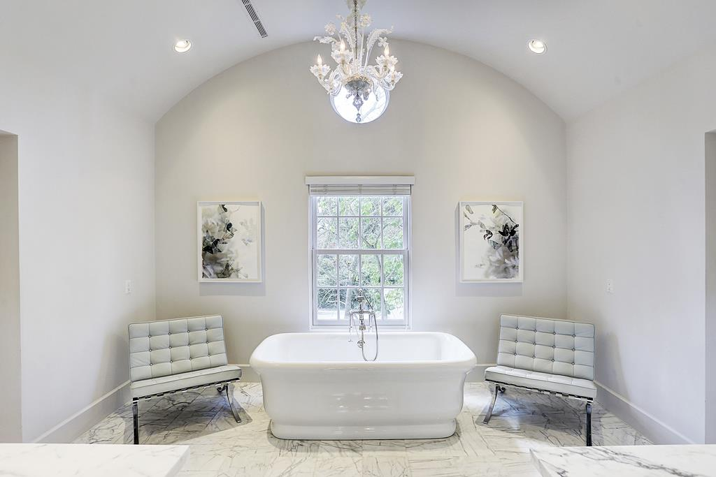 Luxurious soaking tub in elegant white bathroom in Houston home with French inspired decor by M Naeve
