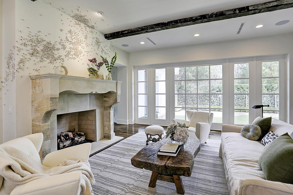 Stunning limestone fireplace beneath modern art by Paul Fleming in a stunning living room designed by M Naeve in Houston