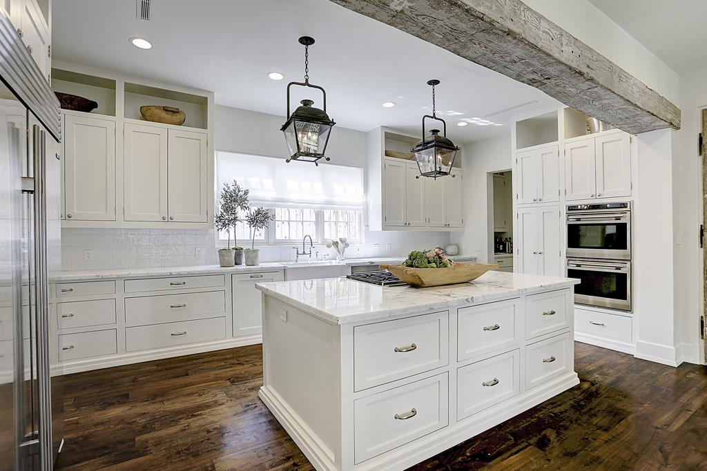 This elegant white kitchen with marble top island and lantern pendants in a gorgeous Houston home with interior design by M Naeve.