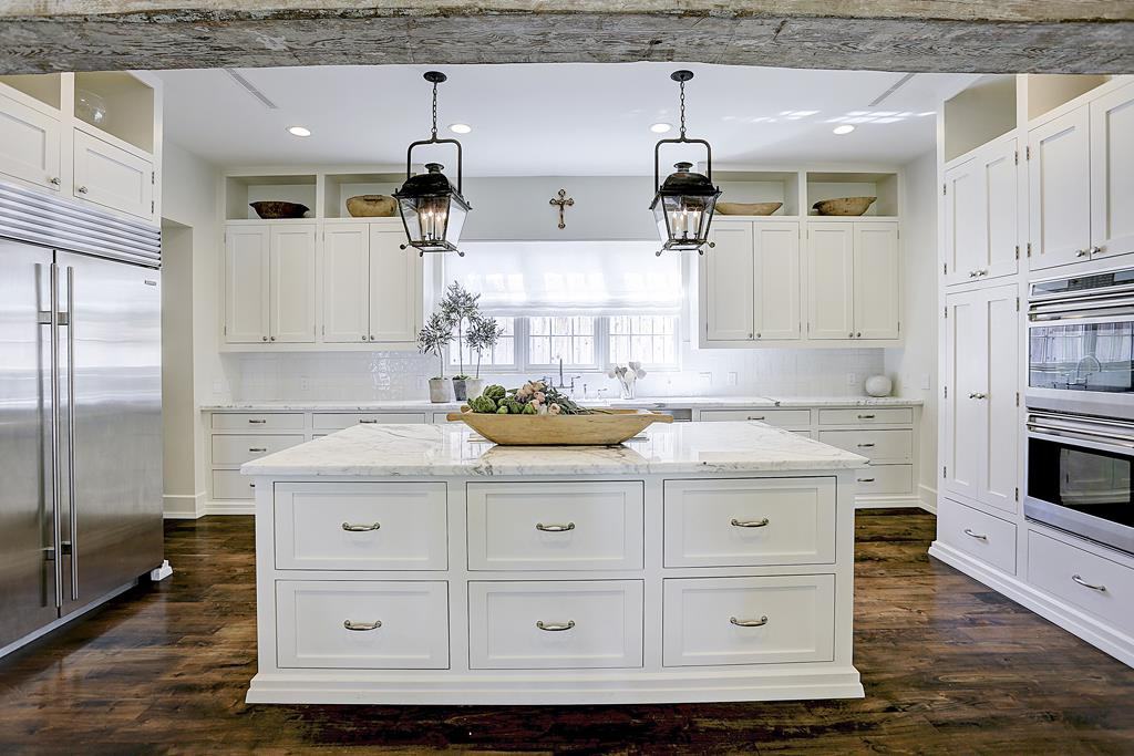 Elegant white kitchen with walnut floors, lantern pendants, and rustic wood beams. Design by M Nave for a European inspired Houston home.