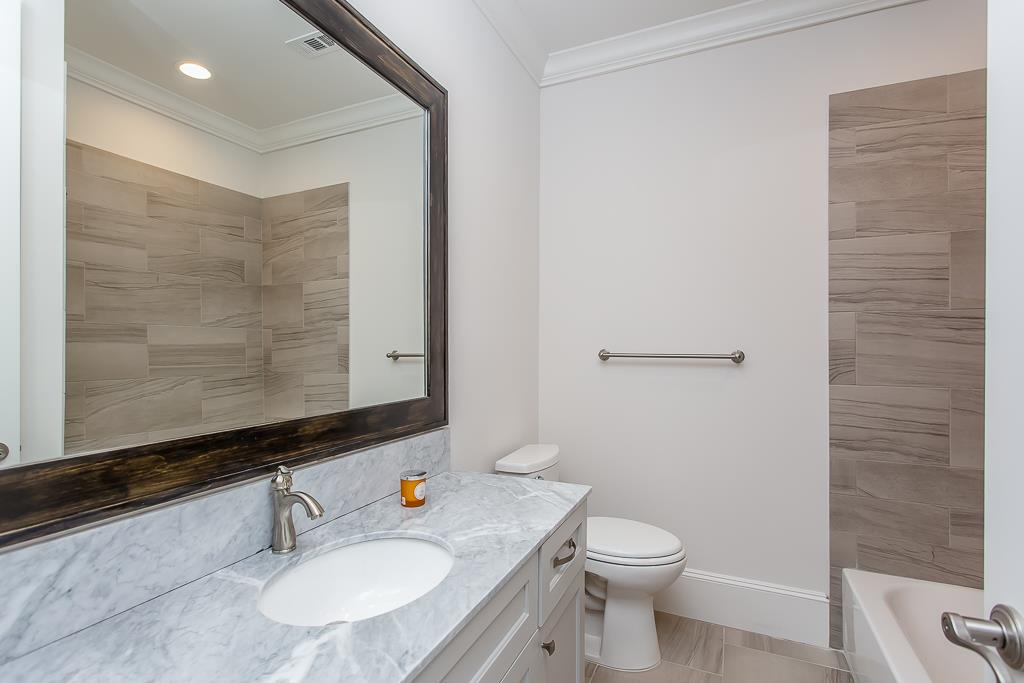 Bed2 Bathroom features Natural Stone Countertop, Custom Framed Mirror &  Cabinetry, Energy Efficient Toilet w/ Soft Close Toilet Seat, Shower w/ Designer Tile ...