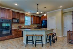 Open kitchen with breakfast bar. Double ovens.