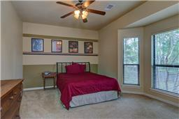 Guest bedroom 3 with ceiling fan with views of back yard.