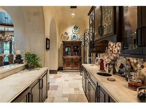 BarThe elaborately-appointed bar includes a wine chiller and a kegerator. Note beveled marble countertops, harlequin-pattern travertine tile backsplash, lighted glass-front cabinets. Iron gates to wine vault open at right rear.