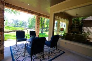 We step outside and this is just one of the sitting areas from which you can enjoy the golf course views.  To help you get your bearings, the downstairs family room is on the other side of the glass wall shown here.